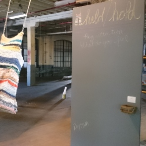 Held/Hold, 2017; used clothes, rope, chain, plywood, chalkboard, chalk; dimensions variable